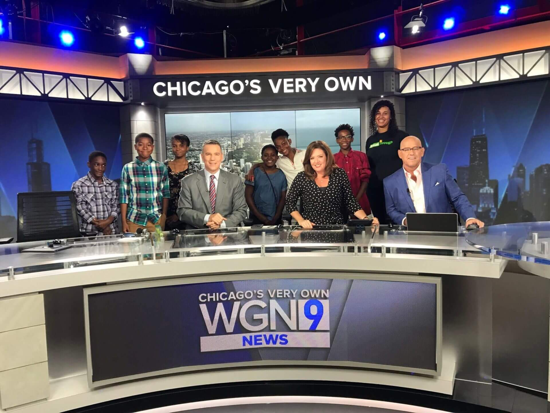 students standing behind news anchors onset at WGN Chicago