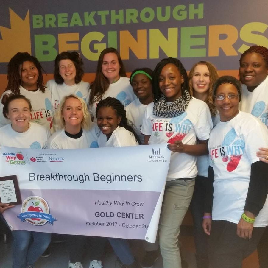 group of teachers posing with Gold certification banner for Breakthrough Beginners preschool