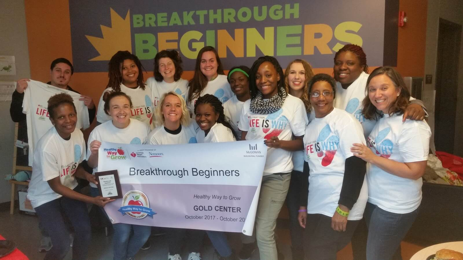 group of teachers posing with Gold certification banner for Breakthrough Beginners preschool