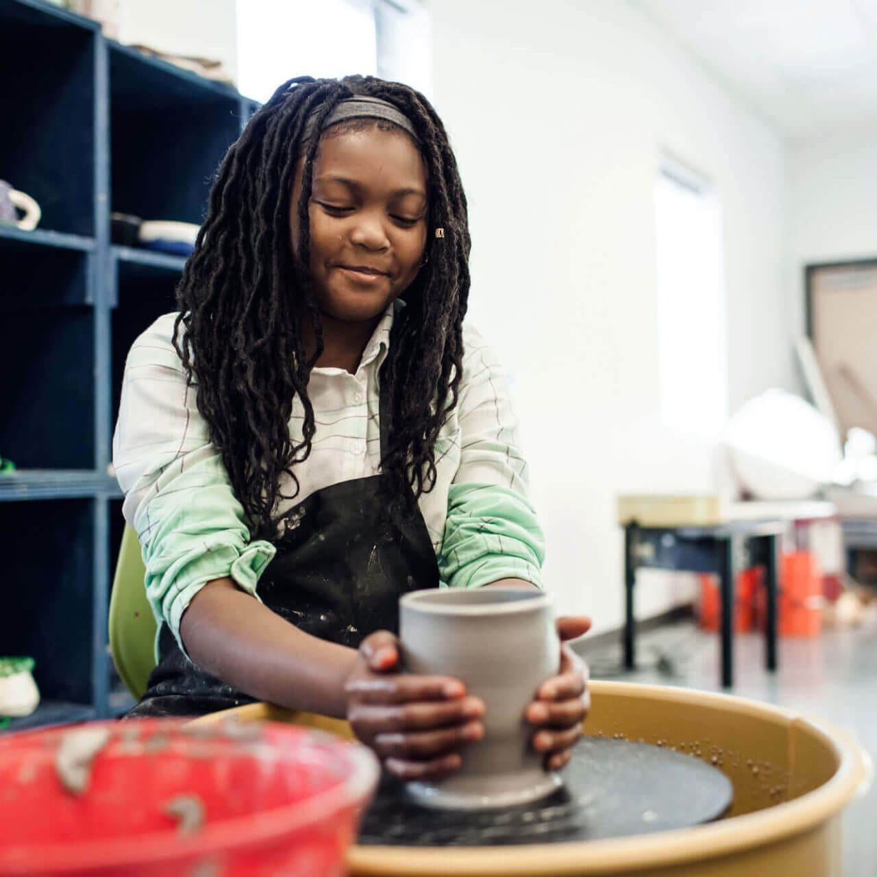 girl shaping pottery on spinning wheel