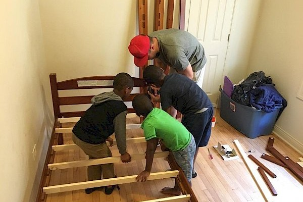 man and boys assembling bed frame while setting up bedroom