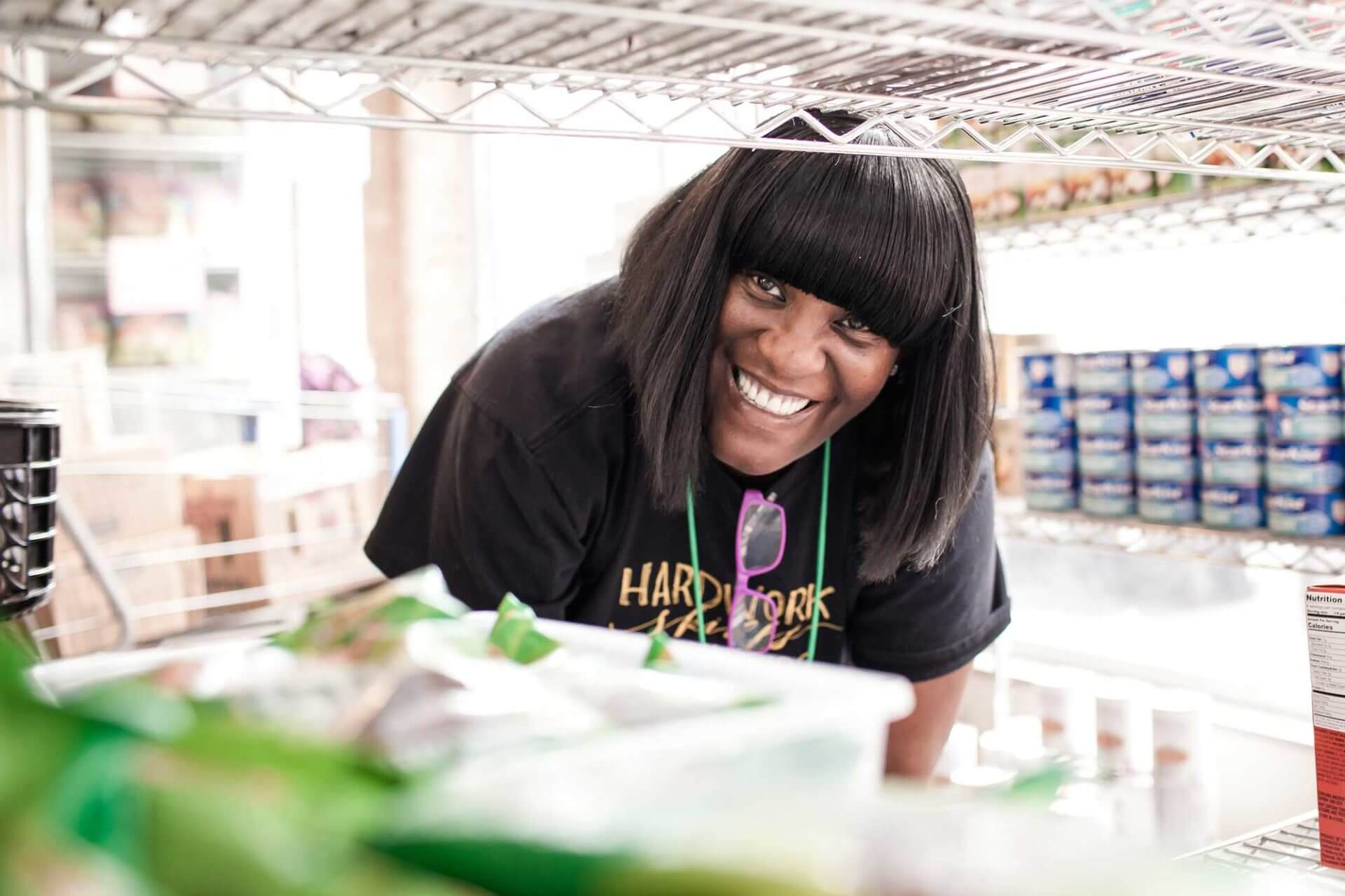 woman smiling while working at the Breakthrough Fresh Market