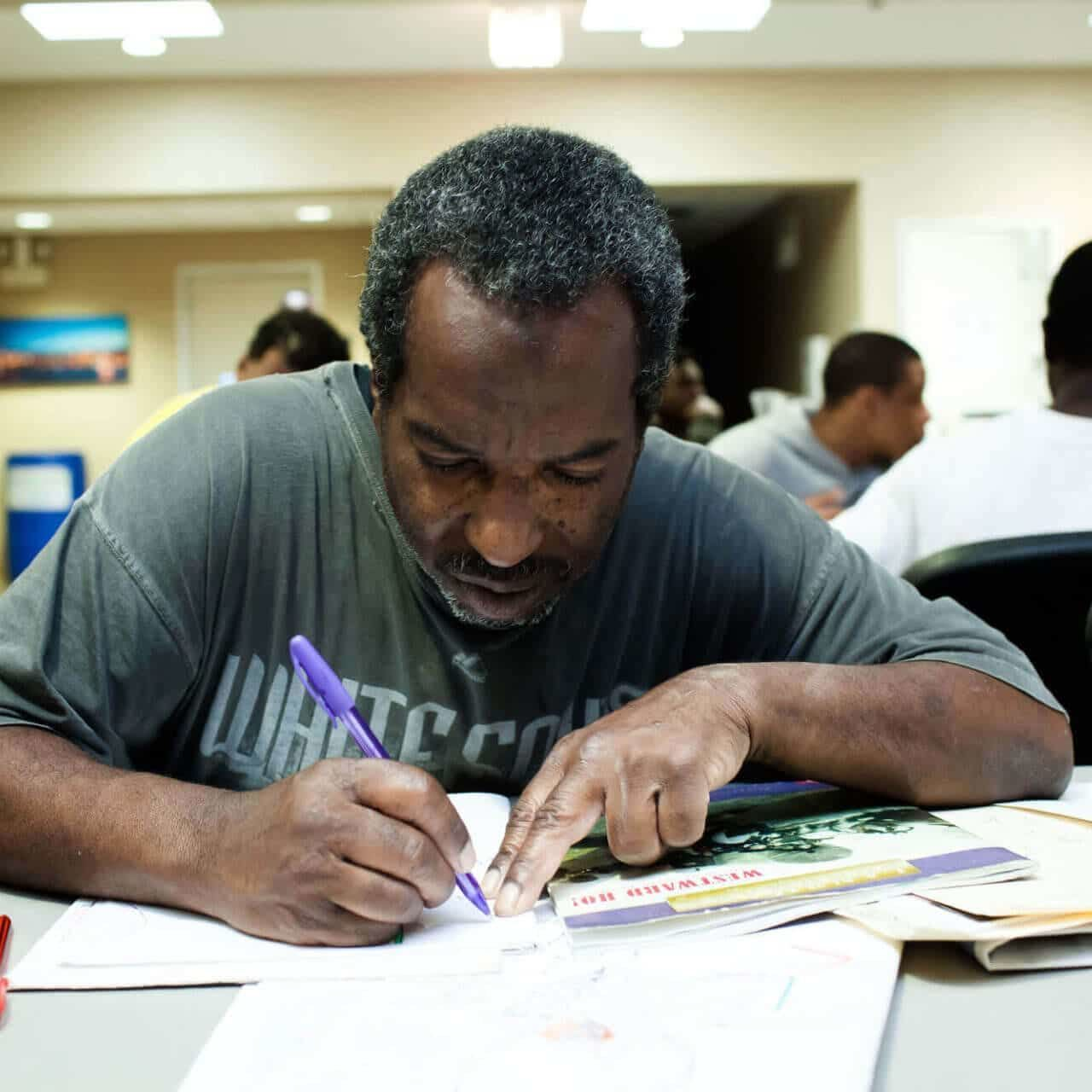 man sitting at table and writing at Breakthrough Men's Center