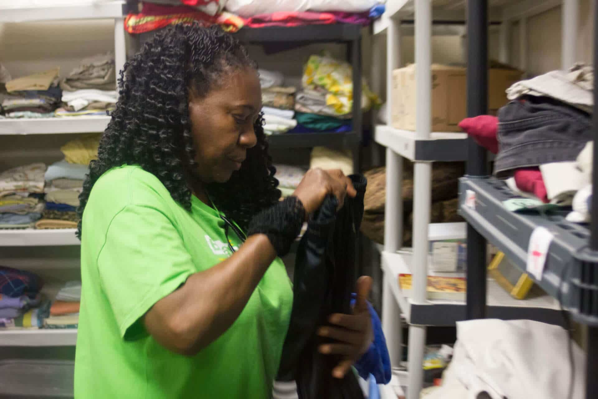woman folding clothes and organizing at Breakthrough Women's Center closet