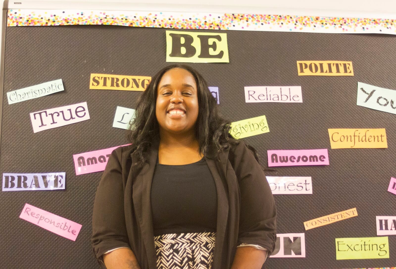 woman smiling in front of bulletin board with positive words