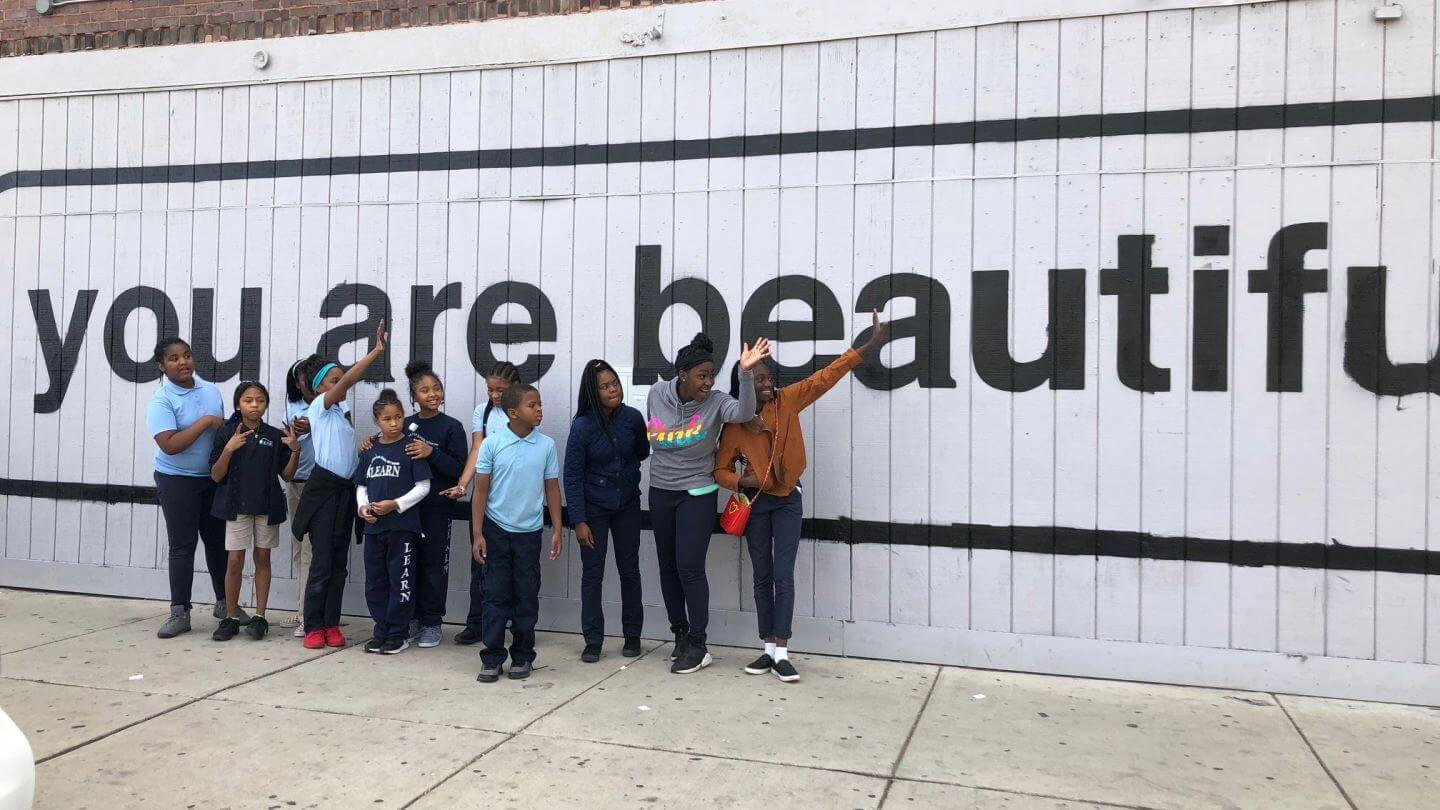 youth standing in front of You Are Beautiful sign on Homan Ave