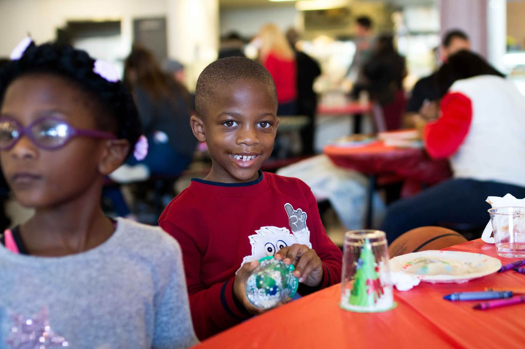 boy making crafts at the Breakthrough Christmas Store