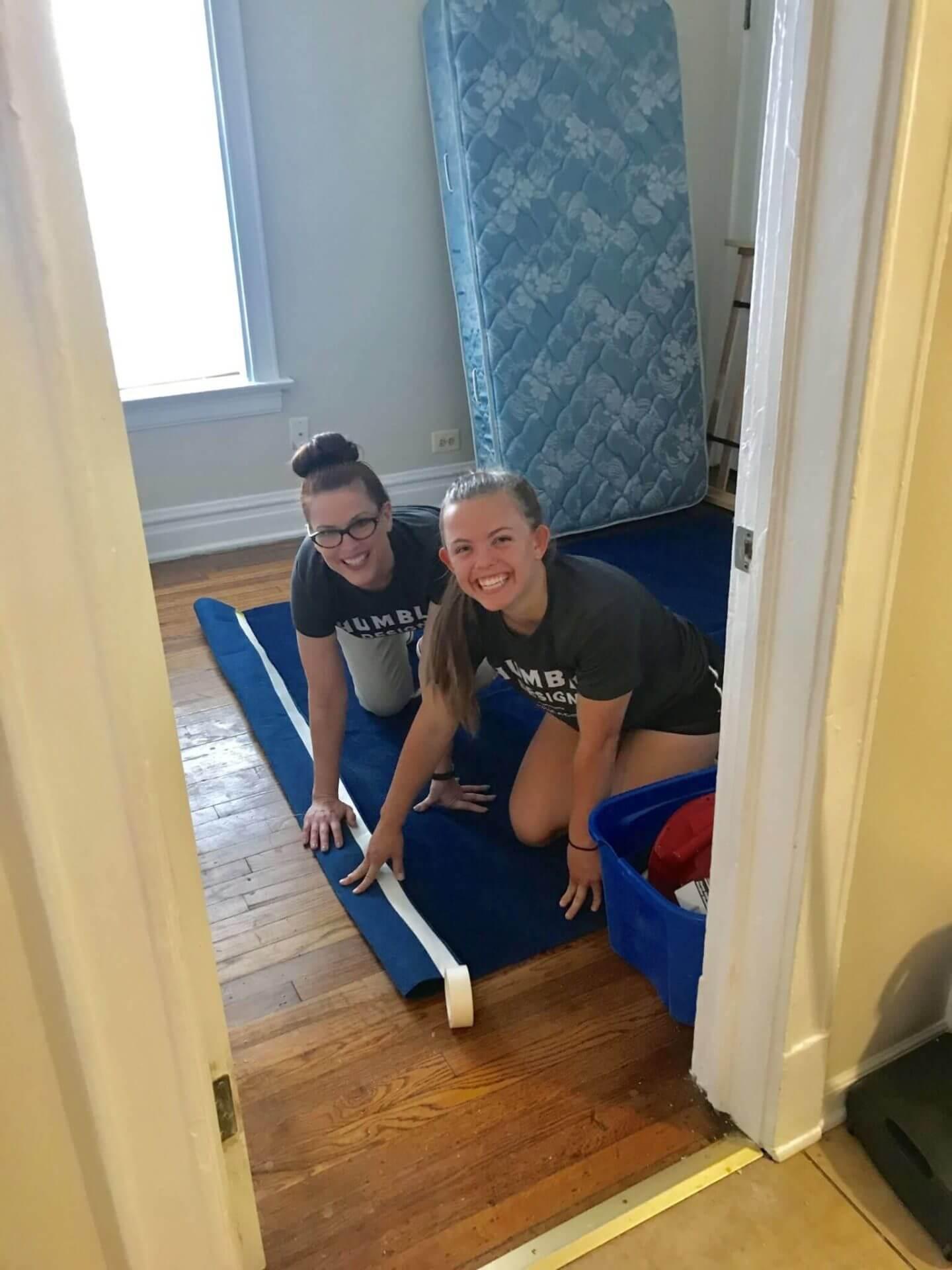 volunteers setting up new furniture in bedroom
