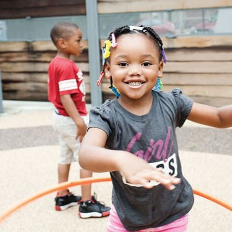 girl hula hooping during recess at Breakthrough Beginners preschool