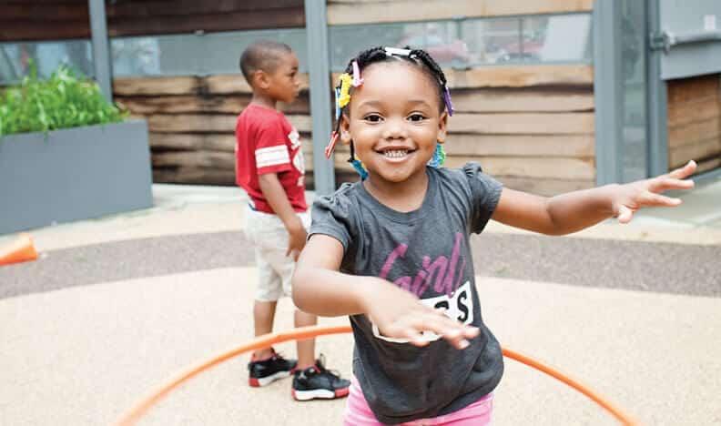 girl hula hooping during recess at Breakthrough Beginners preschool