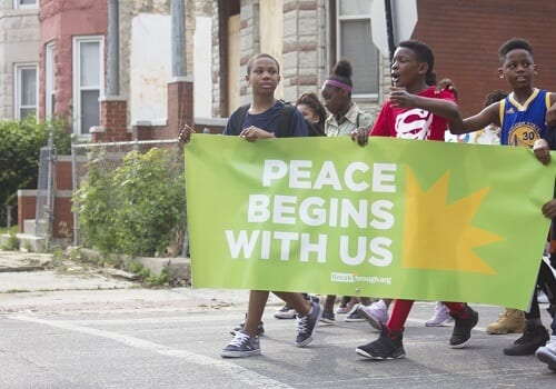 youth marching down East Garfield Park street holding Peace Begins With Us banner