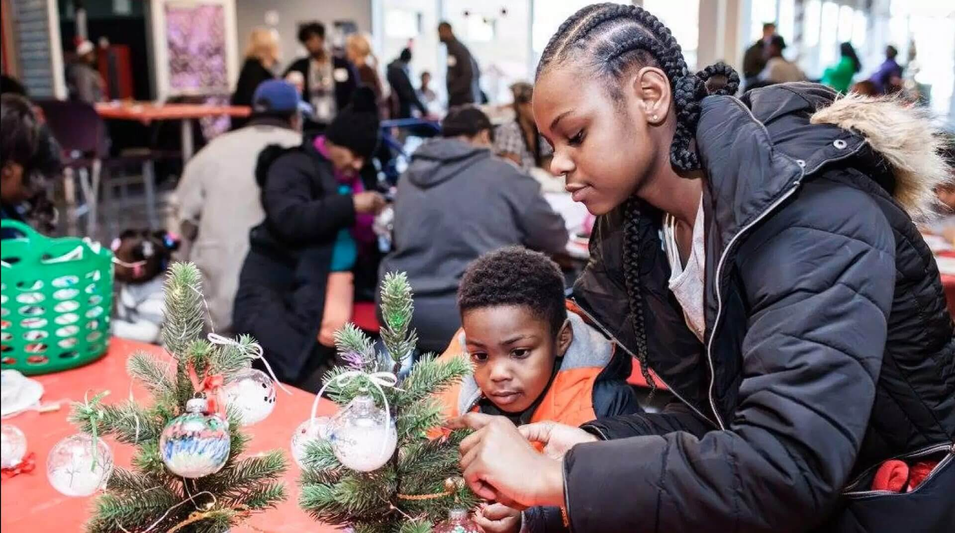 girl and young boy decorate tree at Breakthrough Christmas Store community event