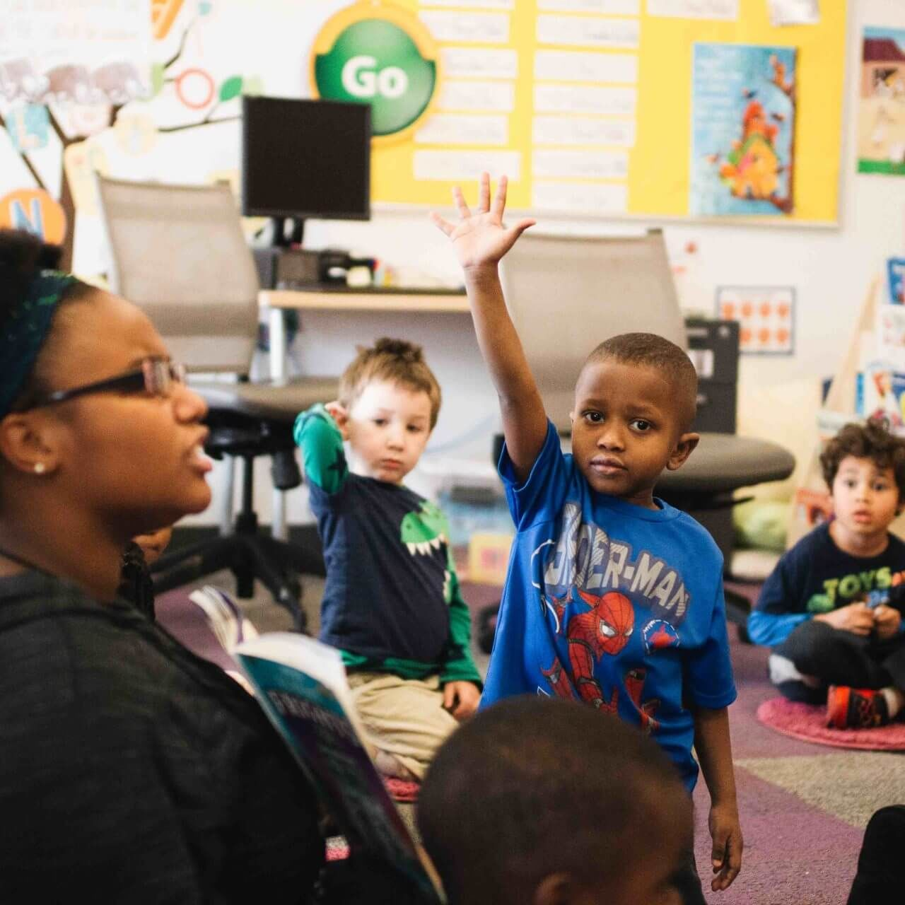 boy raising his hand to answer a question in preschool class