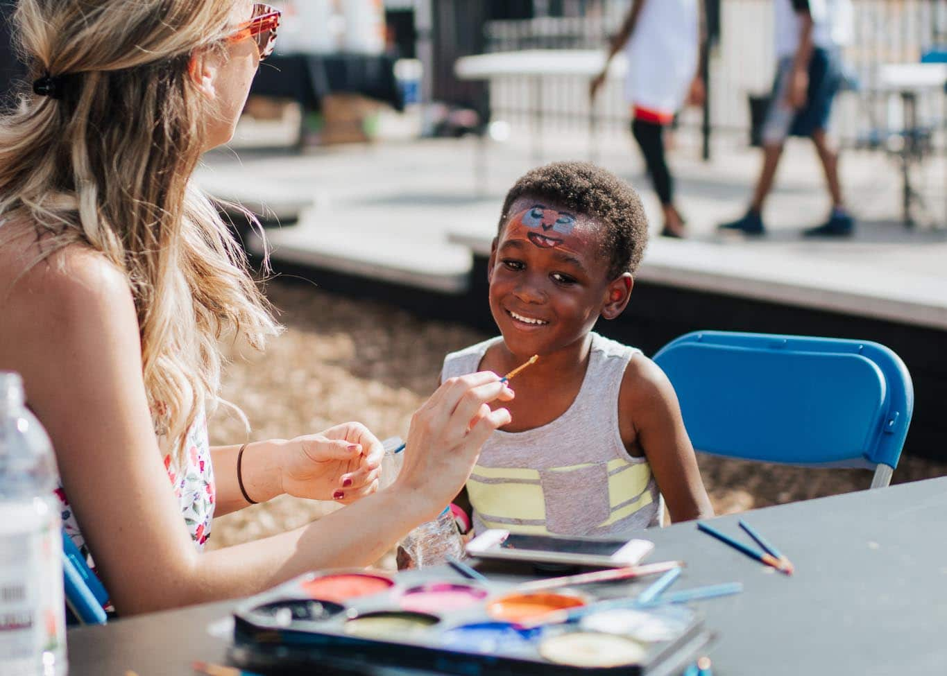 boy getting his face painted at Home Court block party in East Garfield Park