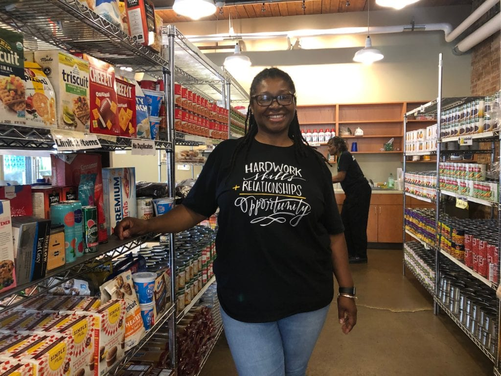 Staff member standing by shelves of food at the Breakthrough Fresh Market
