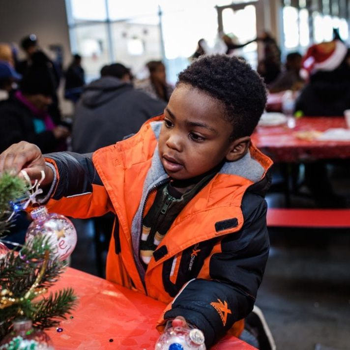Boy decorating a Christmas tree at the Breakthrough Christmas Store